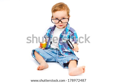 Cute child in glasses with a magnifying glass is experimenting with apple isolated on white background - stock photo