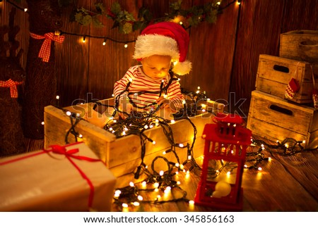 Cute child in Santa Hat sitting in box and playing with Christmas lights - stock photo