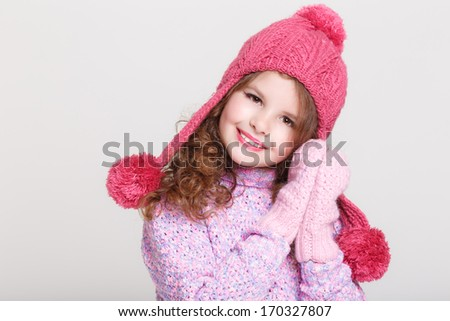 Cute child in winter hat gloves and sweater, little girl portrait in woolen accessories. Winter Fashion. Adorable girl in studio. Happy Little girl winter. Space and white background. - stock photo