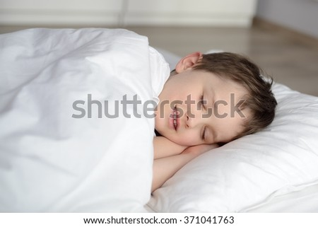 Cute child is sleeping in white bed . Sleeping boy. Sleeping child - stock photo