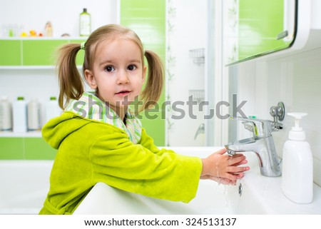 Cute child kid girl washing face and hands in bathroom - stock photo