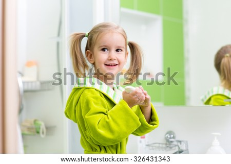 Cute child kif little girl washing hands in bathroom - stock photo