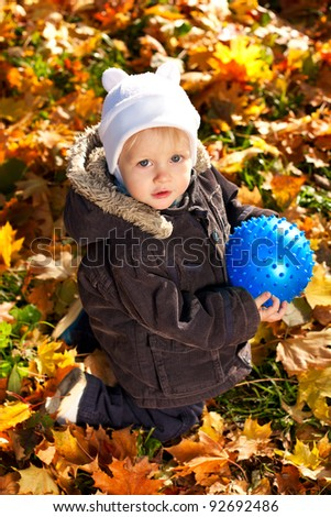 Cute child played with a blue ball in his hands. Golden autumn leaves background - stock photo