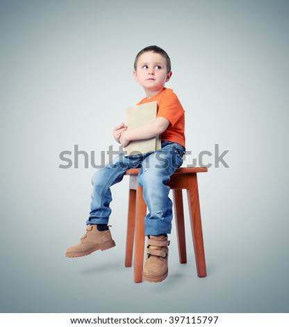 Cute child with a book sitting on a chair - stock photo