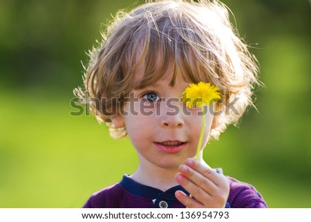 Cute child with dandelion on a green meadow - stock photo