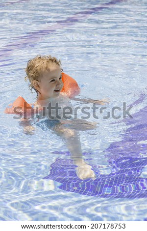 cute child with floats enjoying in the swimming pool - focus on the face - stock photo