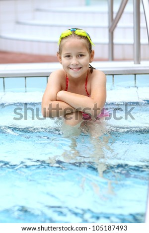 Cute child with goggles relaxing by swimming pool - stock photo