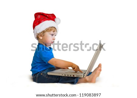 Cute child with Santa Hat and a laptop - stock photo