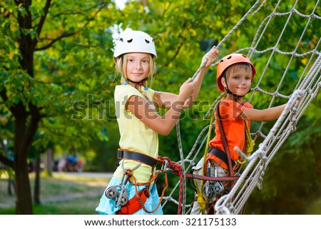 Cute children. Boy and girl climbing in a rope playground structure at adventure park - stock photo