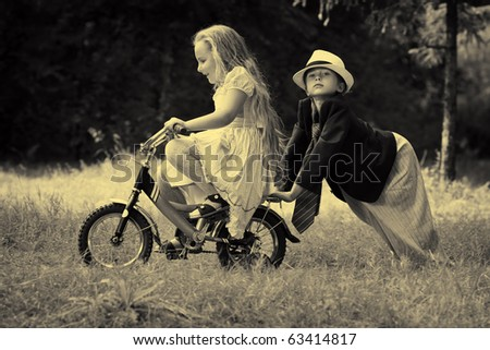 Cute children  is riding a bike in a summer park. Retro style. - stock photo