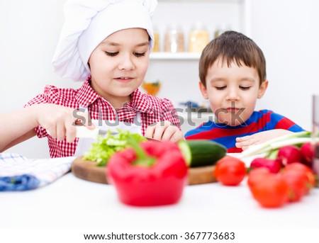 Cute children make vegetable salad - stock photo
