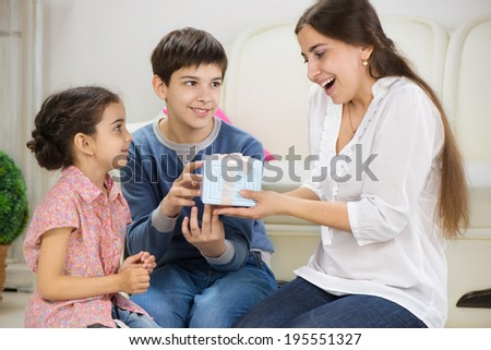 Cute children presenting a gift to mother - stock photo