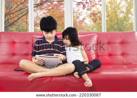 Cute children using digital tablet on sofa at home with autumn tree background - stock photo