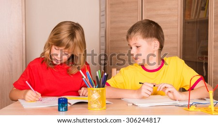 Cute children working on their homework together. Boy and girl doing homework at home. Education and help concept. - stock photo