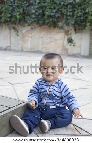 Cute Chinese baby boy playing outdoors, shot in Beijing, China - stock photo