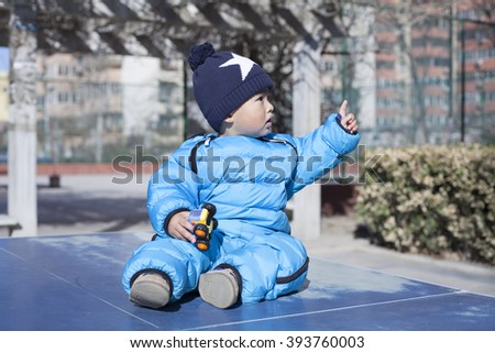Cute Chinese baby boy sitting on a table tennis table, shot in Beijing, China - stock photo