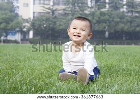 Cute Chinese baby boy sitting on meadow - stock photo