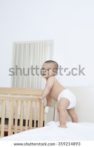 Cute Chinese baby boy standing by his Crib - stock photo