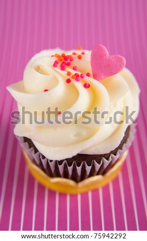 Cute Chocolate Cupcake with Tiny Heart Candy on Top of Vanilla Frosting - stock photo