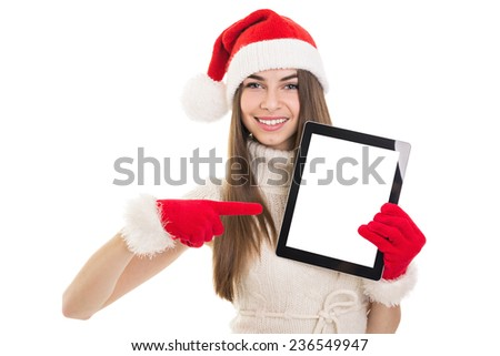 Cute Christmas young woman showing digital tablet screen. Closeup studio shot of happy teenage girl showing tablet screen. Copy space available on screen and in the background. - stock photo