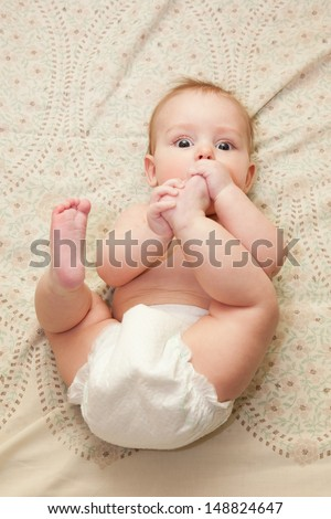 Cute chubby baby laying on his back sucking his leg. Selective focus on eyes. - stock photo