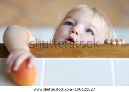 Cute clever baby with beautiful blue eyes and blond hair standing on tiptoes reaching out tasty apricot from high wooden table - stock photo