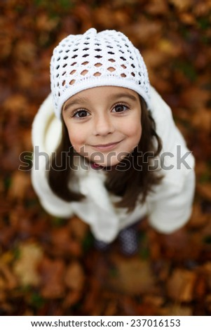 Cute close up portrait of little girl standing on colorful leaves outdoor in fall. Forest foliage. Smiling happy and excited. Entertainment in autumn outdoors.  - stock photo