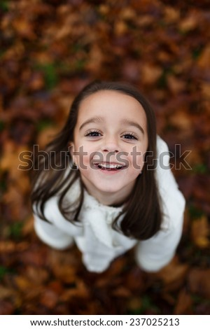 Cute close up portrait of little girl standing on colorful leaves outdoor in fall. Forest foliage. Smiling happy and excited. Entertainment in autumn outdoors.Beautiful adorable wench. - stock photo
