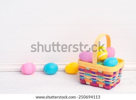 Cute, Colorful Overflowing Easter Basket with Eggs Dyed by Kids on Rustic White Painted Board Table and Background with Empty Blank Room or space for copy, text, or your words.  Horizontal template - stock photo