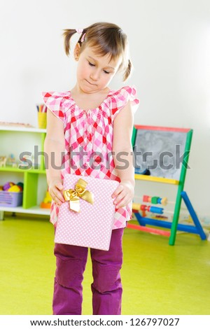 Cute constrained girl with pink present box - stock photo