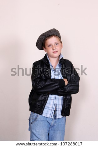 Cute cool boy in black jacket and cap - stock photo