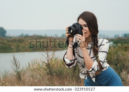 Cute countryside lady with brown hair posing against ranch house and pond with camera. She stands near tall grass and reed against rural scape. She wears jeans dress.   - stock photo