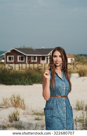 Cute countryside lady with brown hair posing against ranch house. She stands on sand against tall grass. She wears jeans dress. House has one floor. It is made of wood and is painted brown. - stock photo
