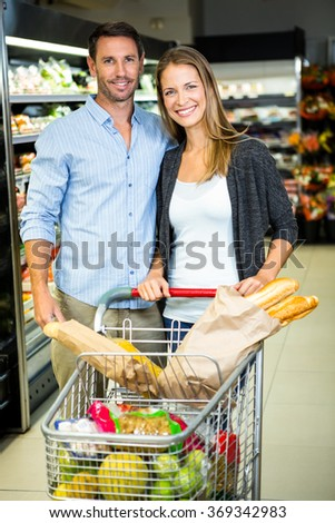 Cute couple doing grocery shopping together at the supermarket - stock photo
