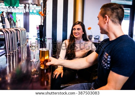 Cute couple having a drink in a bar - stock photo