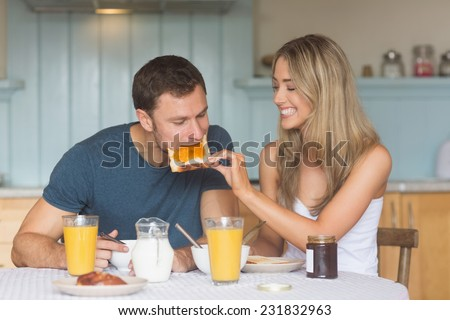 Cute couple having breakfast together at home in the kitchen - stock photo