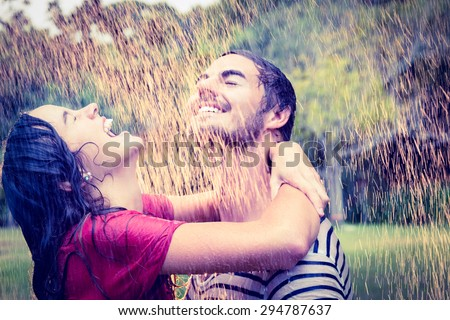 Cute couple hugging under the rain in the park - stock photo