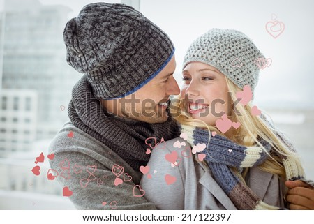 Cute couple in warm clothing smiling at each other against valentines heart design - stock photo