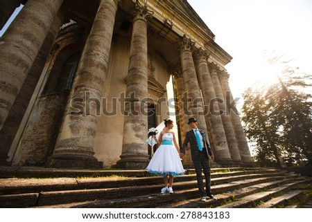 cute couple is holding hands and look each other on background amazing castle - stock photo