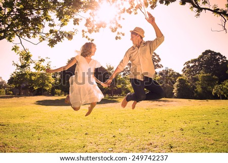 Cute couple jumping in the park together holding hands on a sunny day - stock photo