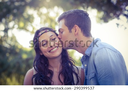 Cute couple kissing in the park on a sunny day - stock photo