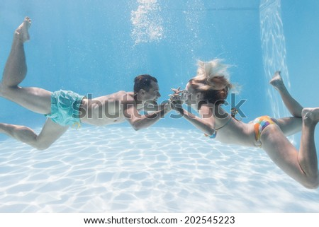 Cute couple kissing underwater in the swimming pool on their holidays - stock photo