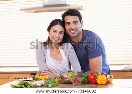 Cute couple looking at the camera in their kitchen - stock photo