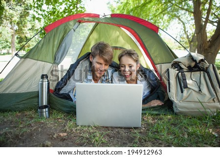Cute couple lying in their tent using laptop on a sunny day - stock photo