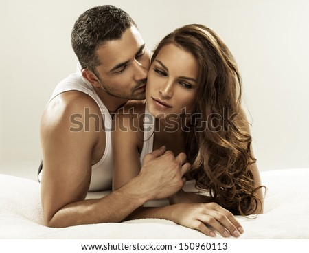 Cute couple lying on the bed - stock photo