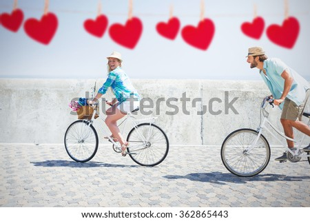 Cute couple on a bike ride against hearts hanging on a line - stock photo