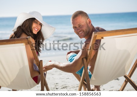 Cute couple on the beach looking at camera while lying on their deck chairs - stock photo