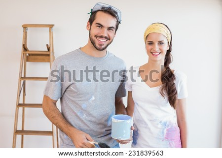 Cute couple redecorating living room in their new home - stock photo