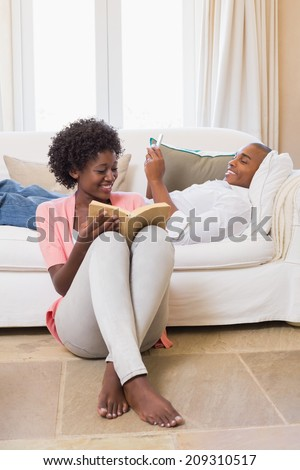 Cute couple relaxing reading book and using smartphone at home in the living room - stock photo