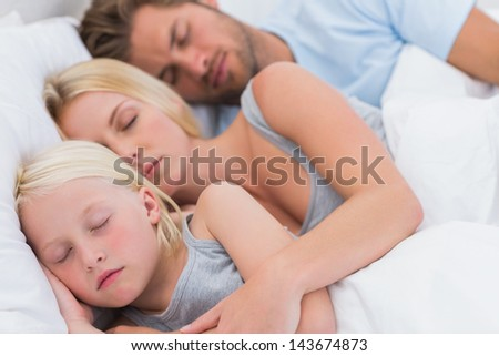Cute couple sleeping with daughter in bed - stock photo